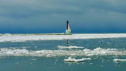 Snow creeping up the Muskegon Breakwater Light